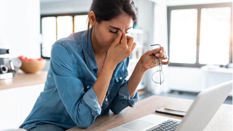 Stresssymptome: Eine Frau hat Stress auf der Arbeit und fasst sich an den Kopf