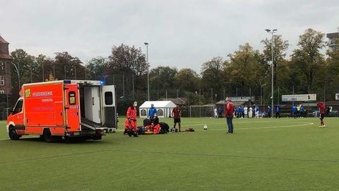 Krankenwagen auf Fußballfeld während Rettungshelfer Berkant Aydin behandeln