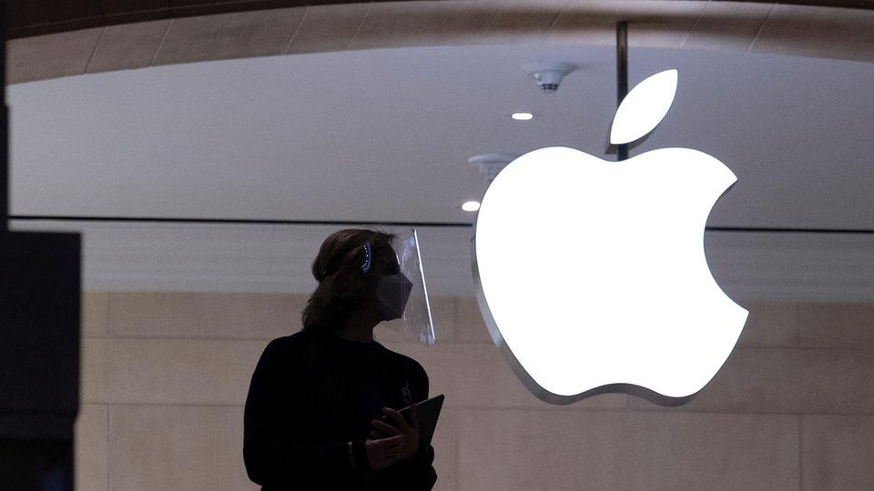 Eine Mitarbeiterin steht vor einer Glaswand mit dem leuchtenden Apple-Logo.