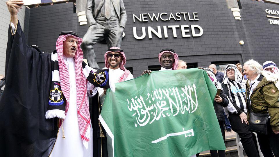 Fans von Newcastle United halten vor dem Stadion eine saudi-arabische Flagge hoch