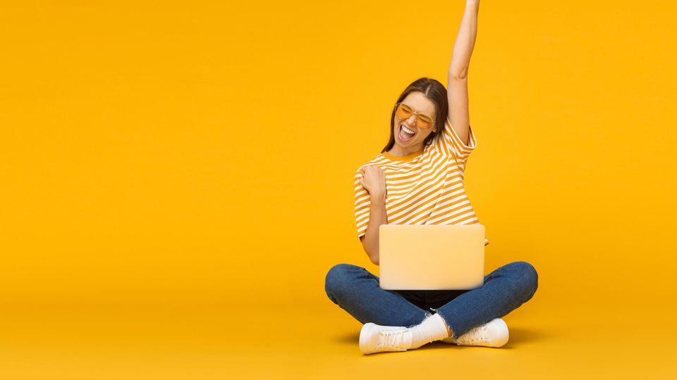 Saturn Gutscheinheft: Eine Frau freut sich über die Angebote bei Saturn.