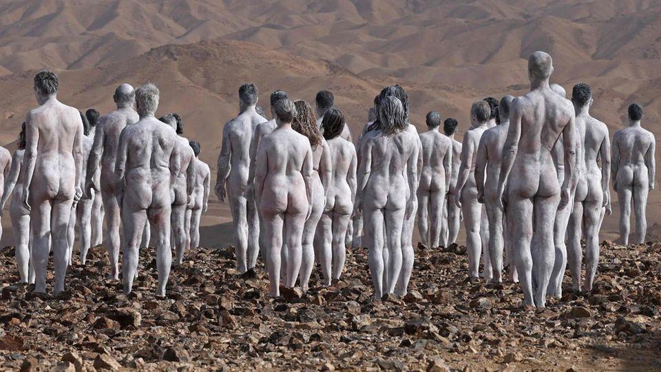 In einer braunen Wüstenlandschaft stehen nackte, weiß angemalte Menschen