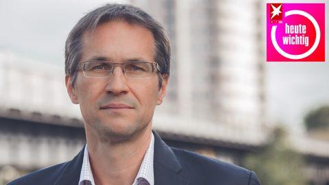 Ein weißer Mann mit angegrautem Mittelscheitel und randloser Brille trägt ein weißes Hemd und ein blaues Jackett