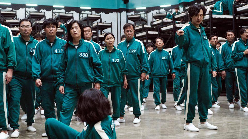 Die Darsteller bei Squid Game tragen alle grüne Trainingsanzüge und weiße Sneaker von Vans.