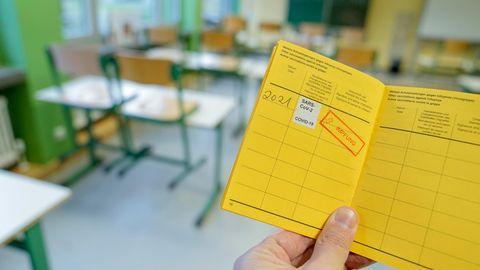 Impfpass mit einer eingetragenen Corona-Schutzimpfung in einem Klassenzimmer.