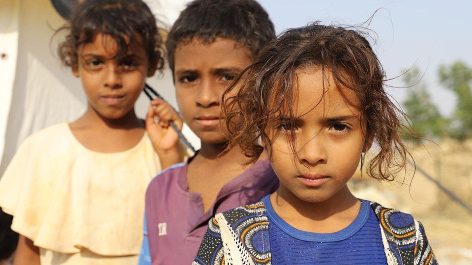 Kinder stehen vor einem Zelt in einem Flüchtlingslager in Jemen, wo sieauf ein Ende des Krieges warten.