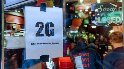 """Ein """"2G""""-Schild hängt vor einer Kneipe"""