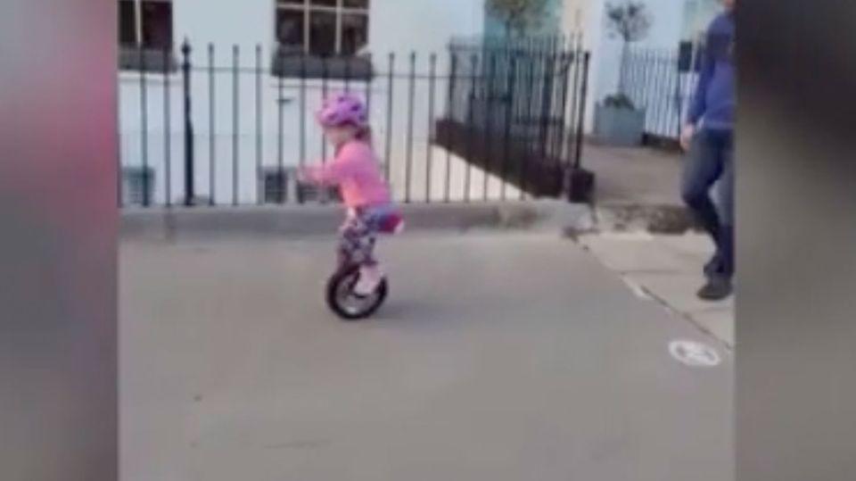 Ein kleines Mädchen fährt auf dem Bürgersteig Einrad.