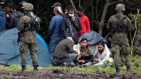 Polnische Sicherheitskräfte umringen Migranten, die an der Grenze zu Weißrussland festsitzen