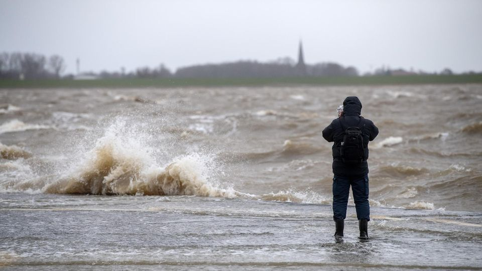 Wetter-Symbolfoto: Ein Mann steht an der Kaimauer während einer Sturmflut