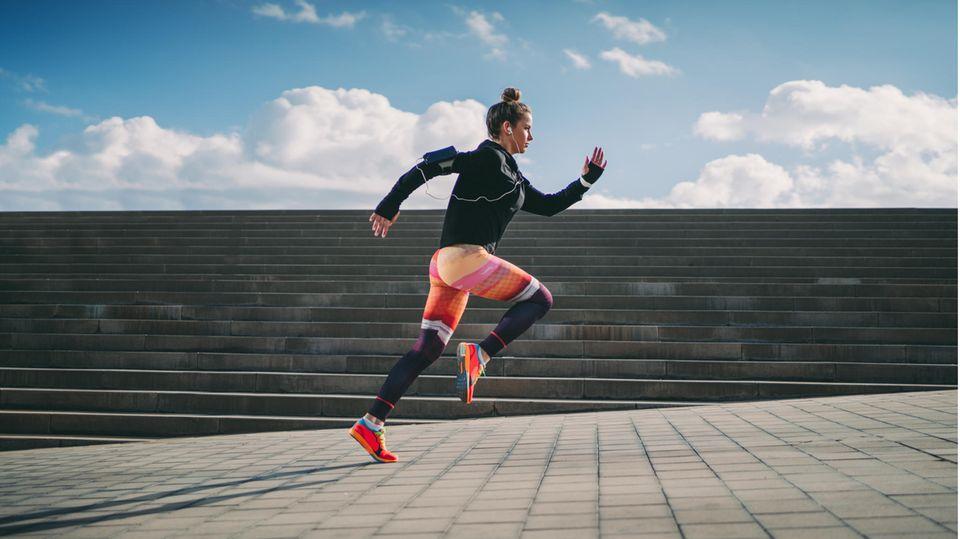 Eine Frau joggt in Lauftights über die Straße