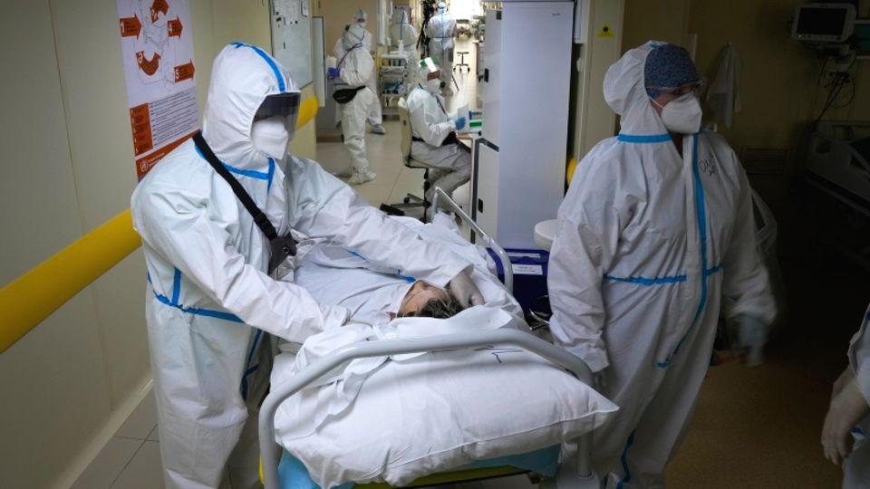 Russland, Moskau: Mediziner verlegen einen Corona-Patienten auf dieIntensivstatio