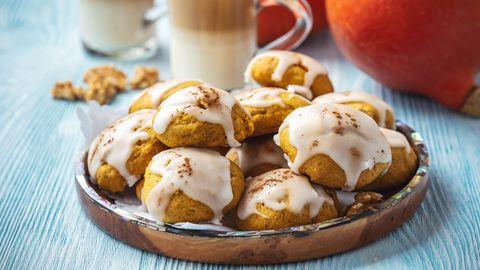Auf einem Teller liegen mehrere Kürbis-Kekse mit Zuckerguss.