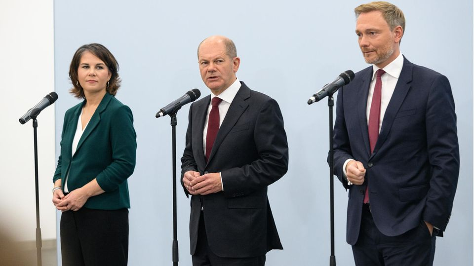 Annalena Baerbock, Olaf Scholz und Christian Lindner stehen vor Mikrofonen.