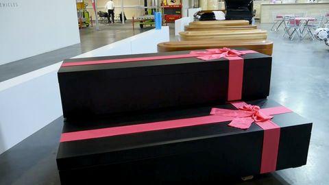 Zwei schwarze Särge mit roten Schleifen werden auf einer Bestattungsmesse ausgestellt.