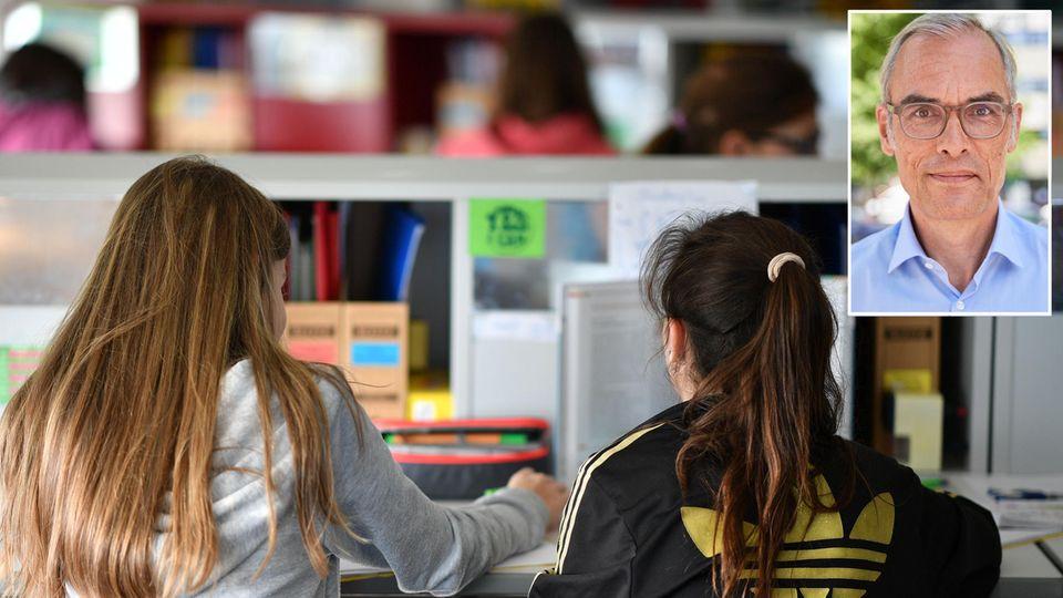 Von hinten sind zwei Schülerinnen mit langen Haaren zu sehen, die gemeinsam in einem Klassenraum sitzen