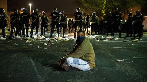 Ein Demonstrant sitzt vor einer Reihe Bereitschaftspolizisten in der Kleinstadt Brooklyn Center am Nordrand von Minneapolis