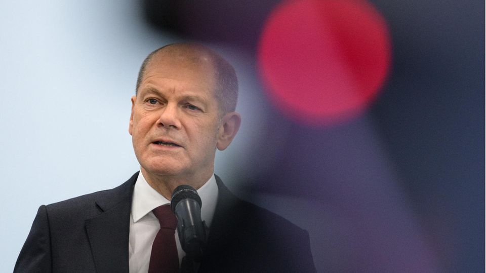 Olaf Scholz am Mikrofon neben einem roten Licht