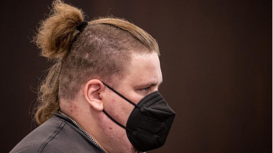 Ein übergewichtiger weißer Mann mit an den Seiten rasierten und oben langen dunkelblonden Haaren