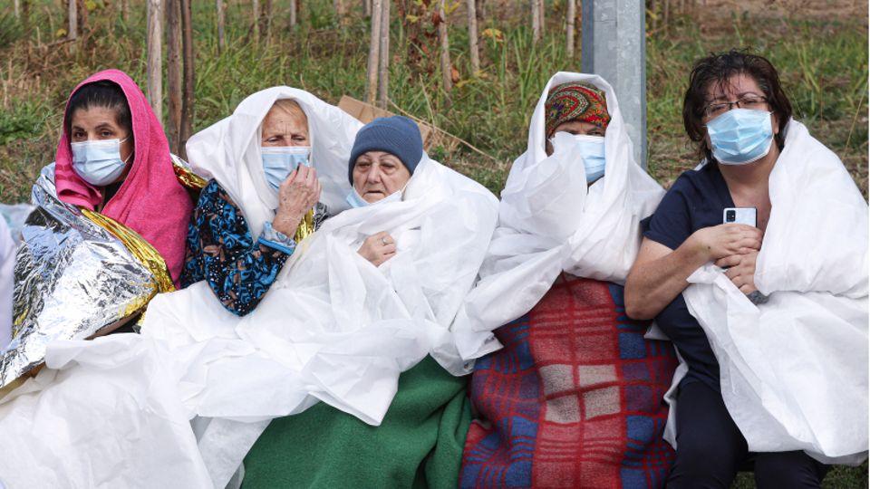 Frauen tragen Mund-Nasen-Schutz und sind in Decken und Laken gewickelt