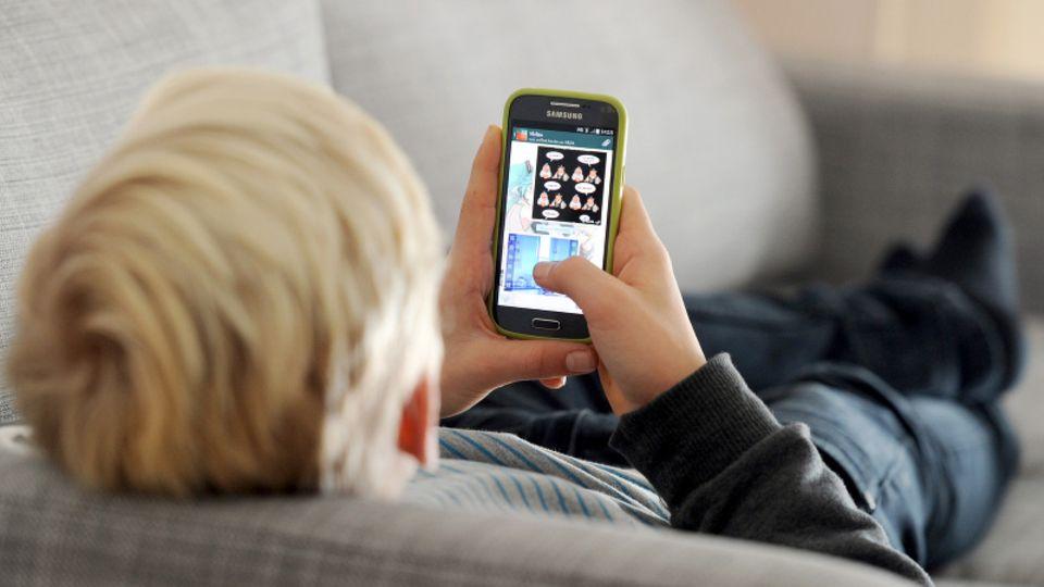 Ein Kind liegt mit einem Smartphone auf einem Sofa
