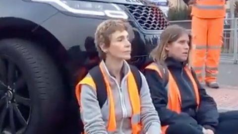 Zwei Frauen sitzen in Warnwesten auf einer Straße. Hinter ihnen steht ein schwarzer SUV