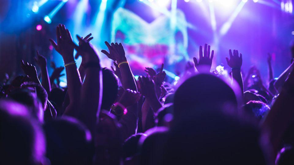 Eine jubelnde Menge tanzt in einem Nachtklub.
