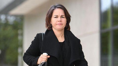 Eine weiße Frau mit schulterlangen, braunen Haaren geht mit Handtasche unter dem rechten Arm an einem hellen Gebäude vorbei