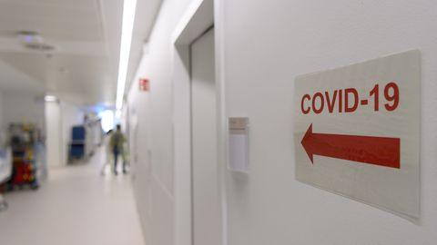 """Ein Schild mit der Aufschrift """"Covid-19"""" und einem Pfeil verweist auf die Corona-Intensivstation des Krankenhauses."""