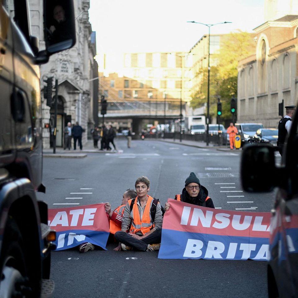 London, Großbritannien. Klimaaktivisten der Gruppe Insulate Britain blockieren eine Straße im Zentrum von London und fordern die britische Regierung auf, die Wärmeisolierung britischer Häuserzu subventionieren.Großbritannien ist bestrebt, vor dem bevorstehenden COP26-Gipfel sein Umweltbewusstsein zu zeigen, sieht sich aber gleichzeitig mit wachsendem Protest von Klimaaktivisten konfrontiert.