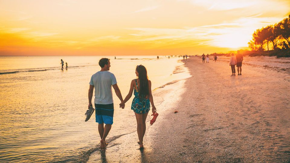 Glückliche Menschen am Fort Myers Beach in Florida bei Sonnenuntergang