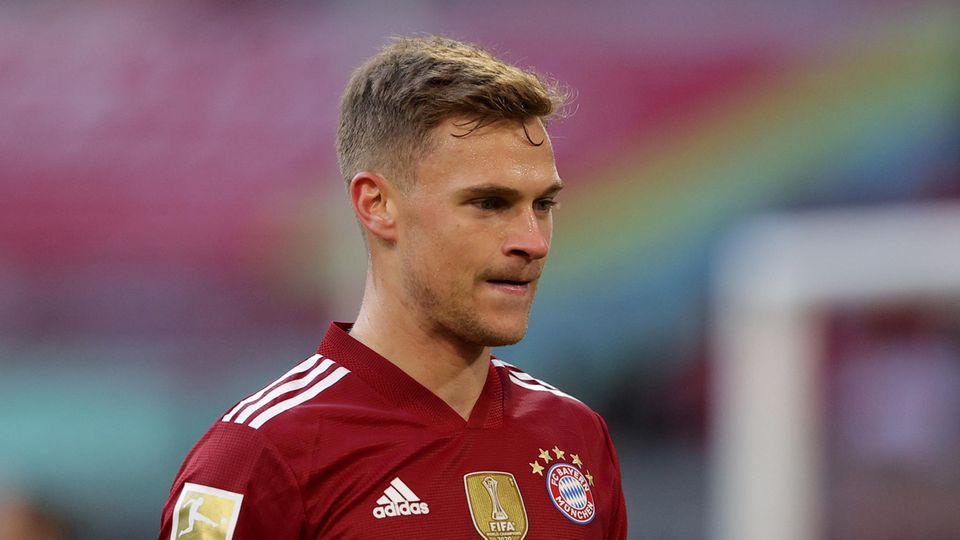 Ein junger weißer Mann mit blondem Seitenscheitel trägt das rot gemusterte Trikot des FC Bayern München