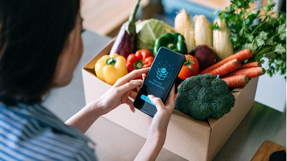 Eine Frau hat Lebensmittel online per Handy bestellt.