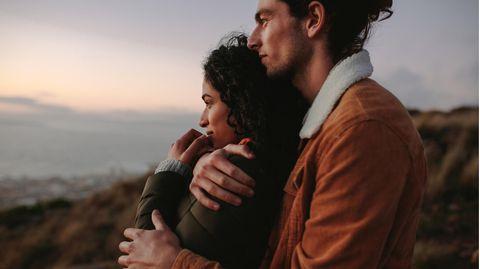 Ein Mann umarmt eine Frau von hinten und sie schauen dabei in die Ferne