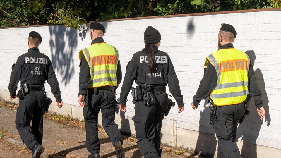 Drei Polizisten und eine Polizistin gehen in Uniform-Overalls auf einem Fußweg an einer weißen Backstein-Gartenmauer entlang