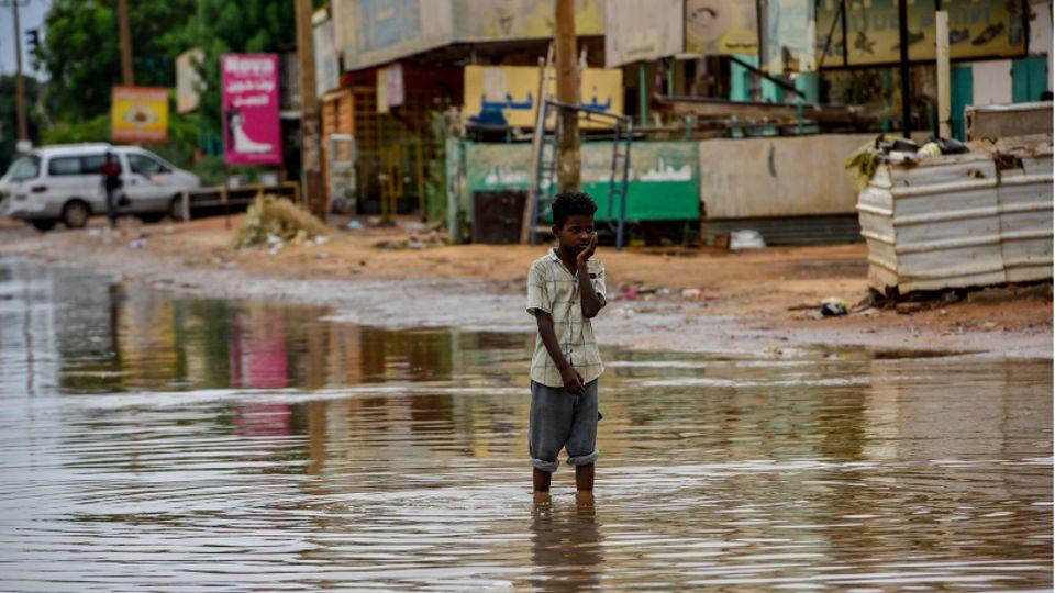 Ein Junge steht in einer überfluteten Straße