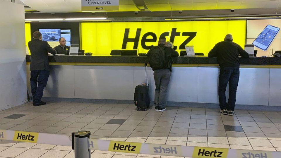 Menschen werden an einem Schalter des Autovermieters Hertz bedient.