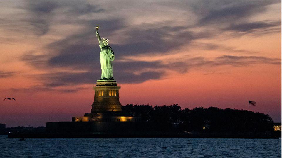 USA, New York: Die Freiheitsstatue wird bei Abenddämmerung angestrahlt