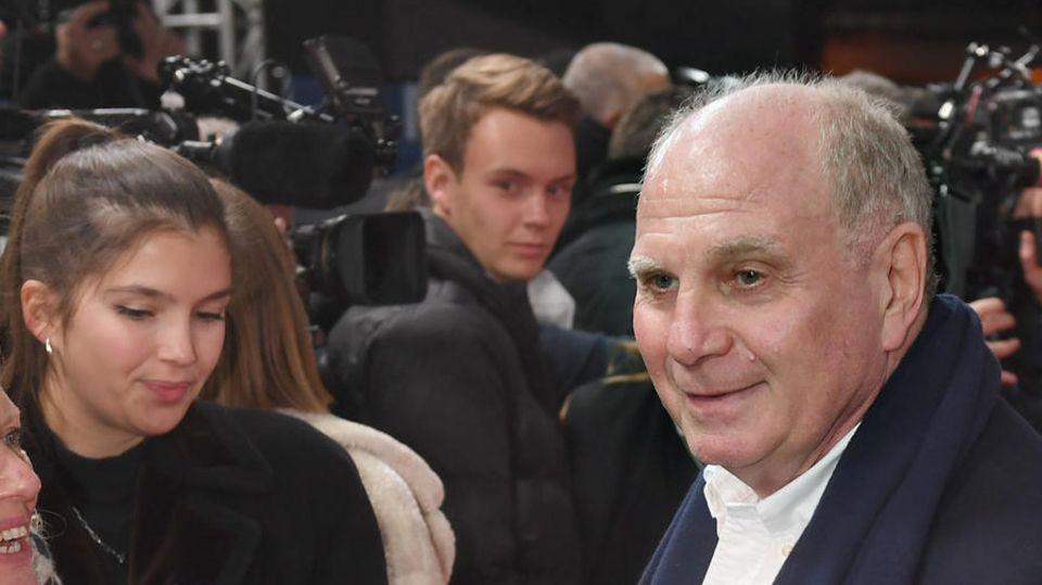 Auf einem roten Teppich steht ein weißer älterer Mann mit Bauchansatz und spricht lächelnd in ein blaues Mikrofon