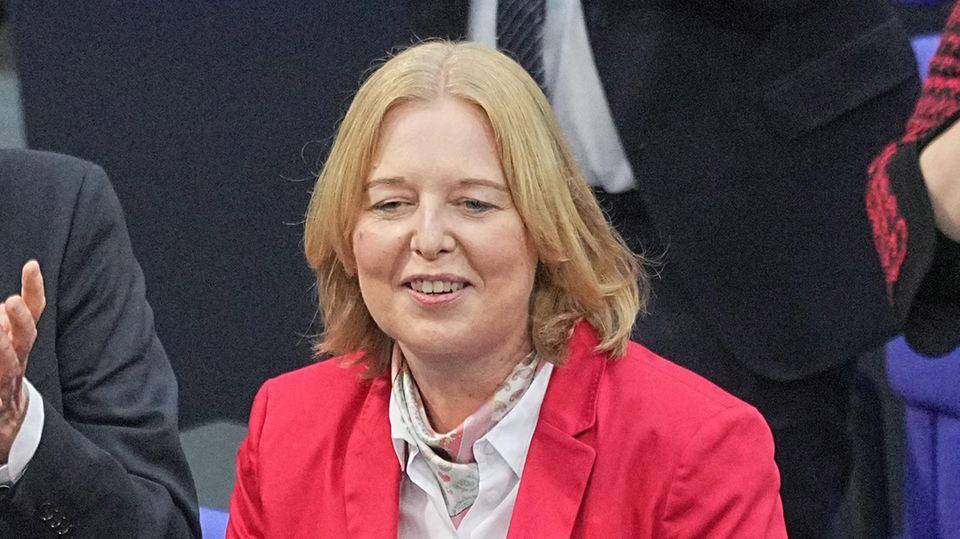 Eine weiße mittelalte Frau mit schulterlangen blonden Haaren und in rotem Blazer lächelt und legt dankend die Hände zusammen
