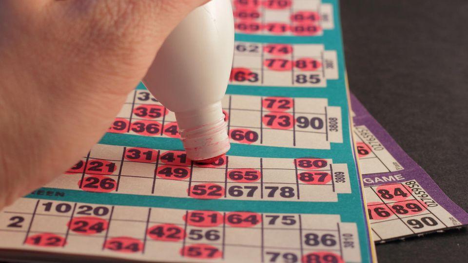 Jemand kreuzt mit einem Stift Zahlen auf einem Bingo-Bogen an.