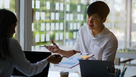 Ein Mann und eine Frau sitzen am Tisch und verhandeln.