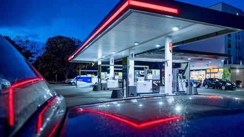 In der Dämmerung spiegelt sich das rote Licht eines Tankstellendaches im Lack eines Autos