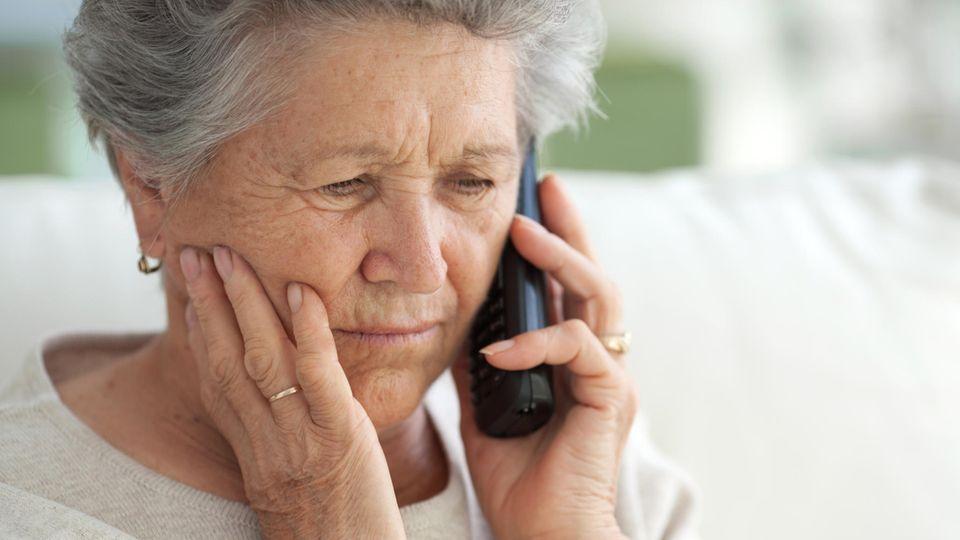 Eine Seniorin hat den Hörer ans Ohr gelegt