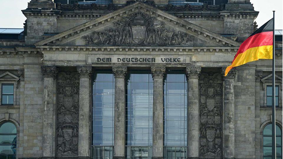 Vor dem Reichstagsgebäude weht eine Deutschland-Flagge an einem Flaggenmast