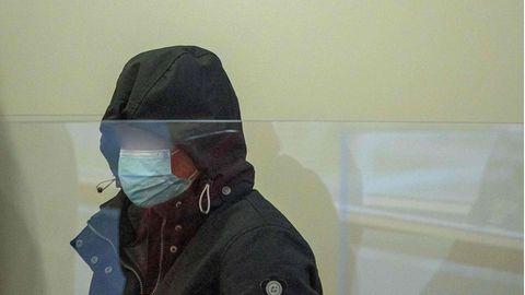 Hinter einer Plexiglasscheibe sitzt eine Frau, die sich in einer dunkelblauen Kapuze und hinter einer OP-Maske verbirgt
