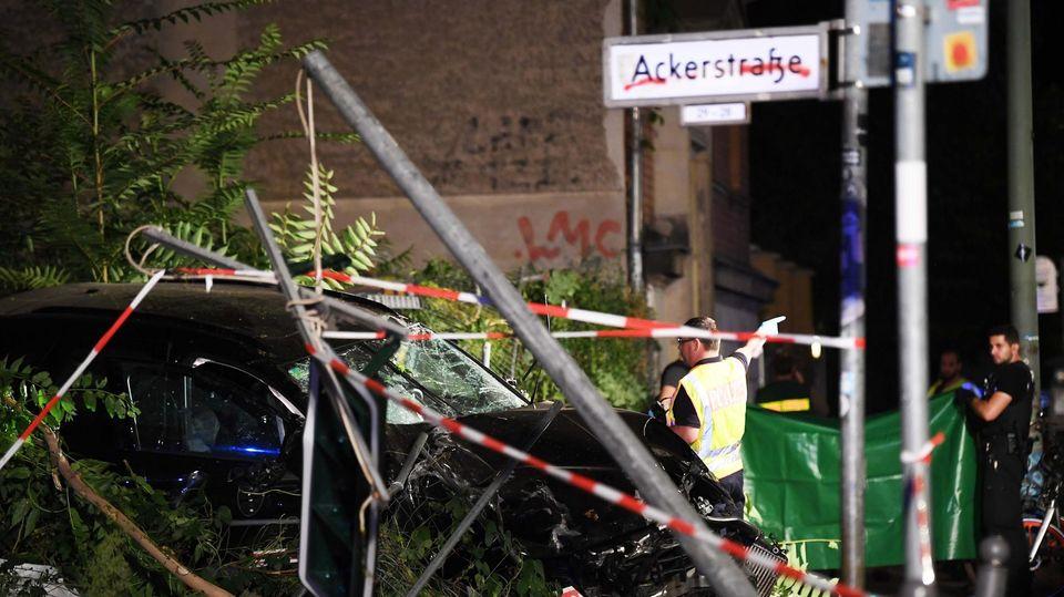 An einem zerstörten Auto halten Polizisten ein Plane