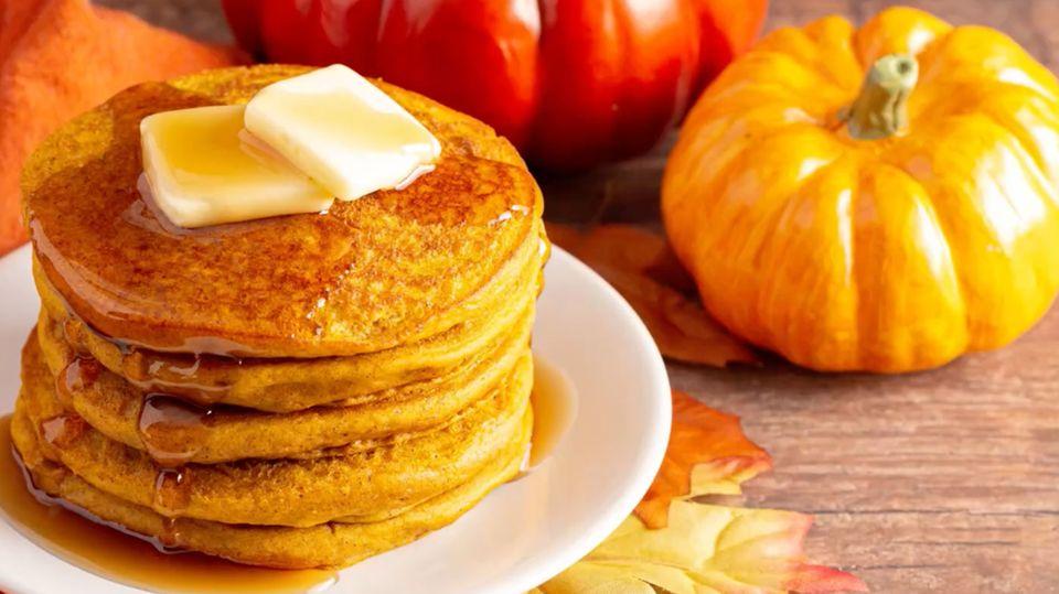 Pancakes auf einem Teller, dekoriert mit Kürbissen und Herbstlaub.