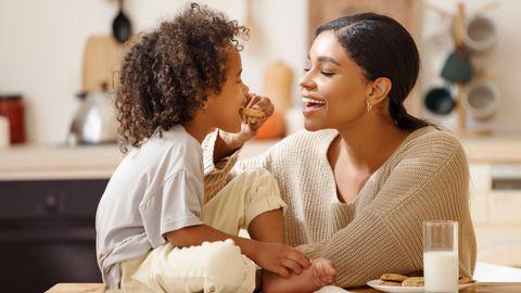 Eine Frau isst mit ihrem Kinde Kekse