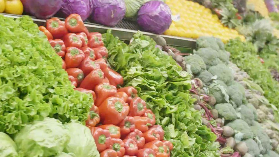 Ein reich gefüllltes Gemüseregal mit Salat, Paparik und vielem mehr.